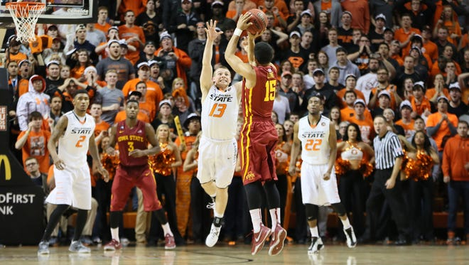 Iowa State guard Naz Long (15) shoots a 3-point shot at the buzzer defended by Oklahoma State guard Phil Forte (13) to send the game into the triple overtime at Gallagher-Iba Arena last season. Iowa State defeated Oklahoma State 98-97.