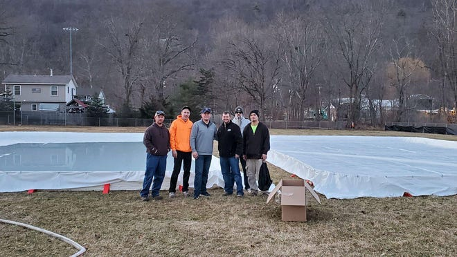 Duncan McCarthy, second from left, stands with volunteers and Mayor Jesse Dwyer, third from left, and Sean Aronse, fourth from left, at the newly installed ice rinks at Helen Kelly Field in Greenwood Lake.