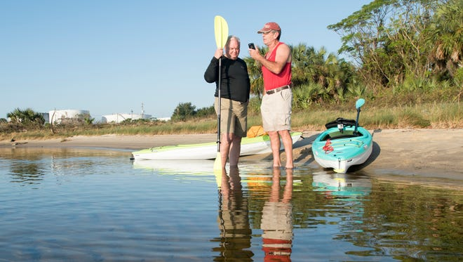Jerry Holzworth, left, and Dan Lindemann conduct an interview with a local radio station about their lawsuit while standing on the shore of  Bruce Beach in Pensacola on Tuesday, November 7, 2017.  A fish hatchery is proposed to be built on the Bruce Beach property.