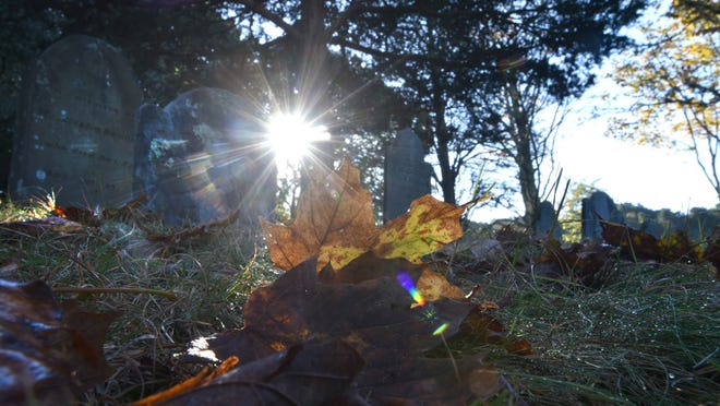 The rising sun lights up a fallen maple leaf colors the headstones of the old Sears Cemetery off Old County Road in Dennis.