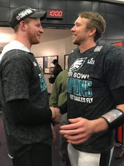 Eagles quarterbacks Carson Wentz, left, and Super Bowl LII MVP Nick Foles meet up in the victorious locker room Sunday night as Philadelphia celebrated its Super Bowl LII victory over the New England Patriots at U.S. Bank Stadium in Minneapolis.