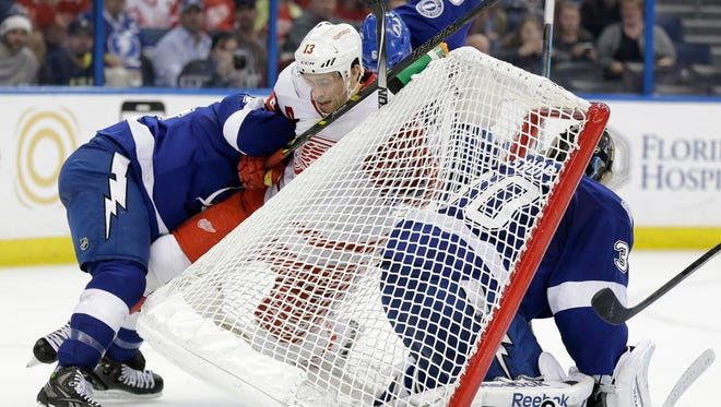 Pavel Datsyuk is pinned to the back of the goal by  Lightning players during the third period Thursday night.