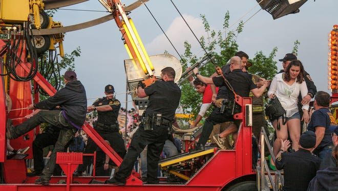 Police officers, firefighters, technicians, and strangers help hold the ferris wheel from moving, while students and community members are pulled from the ride to safety at Late Nite's annual Carnival on Friday night.