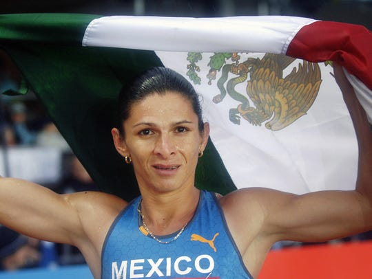 Ana Guevara sostiene la bandera mexicana tras ganar