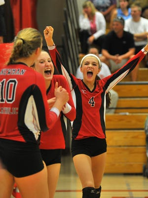 Newman's Rylie Vaughn, right, Taylor Hackel (12), and Mariah Whalen celebrate their victory over Marathon during Tuesday's Marawood Conference-South Division girls volleyball game at Newman Catholic High School in Wausau.