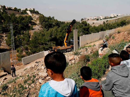 Palestinians from the Shuafat refugee camp in east Jerusalem watch as Israeli forces replace the collapsed sections of the controversial Israeli separation wall, dividing the camp from the Israeli settlement of Pisgat Zeev (L) after it collapsed due to heavy rainfall and floods.