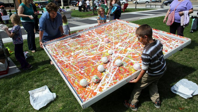 Hunter Olson,Neenah. helps lift a canvas at the Marble Painting area during the 2016 Fox Cities Community Art Day in Houdini Plaza, Appleton.