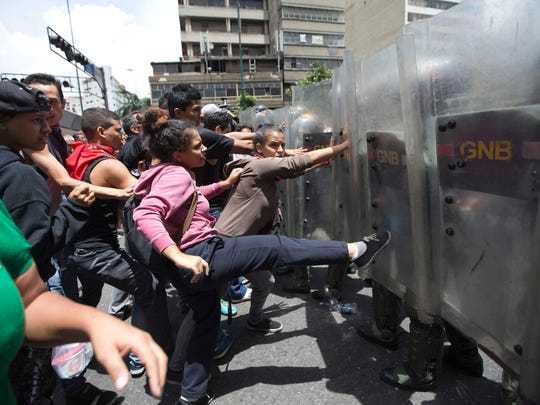 FILE - In this June 2, 2016 file photo, a woman kicks National Guard soldiers' shields during a protest demanding food, near Miraflores presidential palace in Caracas, Venezuela, triggered by rising frustration with food shortages and inflation. President Nicolas Maduro has greatly enhanced the power of his generals, who have become an indispensable crutch as the economy has tanked and street protests against the deeply-unpopular administration grow. (AP Photo/Ariana Cubillos, File)