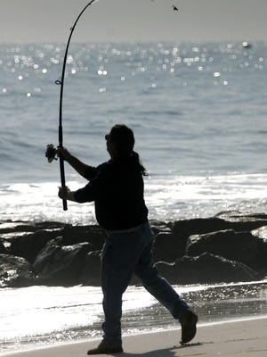 A surf fisherman casts a line on a Delaware beach.