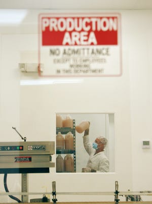 A lab technician with Ecological Laboratories in Cape Coral removes products from a conveyer belt while working in the laboratory on Wednesday.