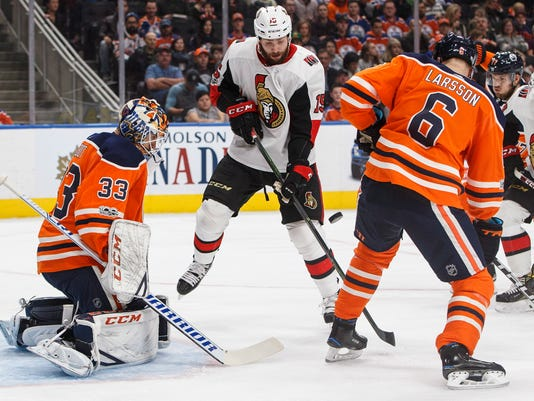 Ottawa Senators' Zack Smith (15) tries to tip the puck past Edmonton Oilers goalie Cam Talbot (33) as Adam Larsson (6) defends during the first period of an NHL hockey game Saturday, Oct. 14, 2017, in Edmonton, Alberta. (Jason Franson/The Canadian Press via AP)