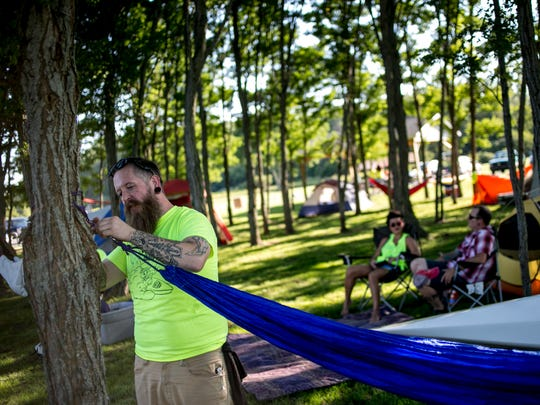 Bill Holmes, of Port Huron, hangs his hammock among other campers during the Paddle and Pour festival Friday, August 26, 2016 at Baker's Field in Port Huron Township.