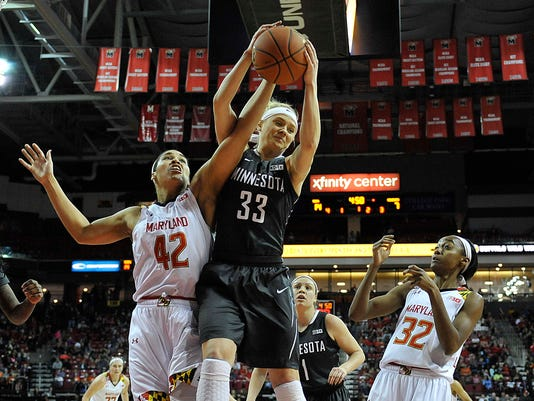 Minnesota's Carlie Wagner, center, grabs a rebound between Maryland's Brionna Jones, left, and Shatori Walker-Kimbrough during the first half of an NCAA college basketball game, Sunday, Feb. 28, 2016, in College Park, Md. (AP Photo/Gail Burton)