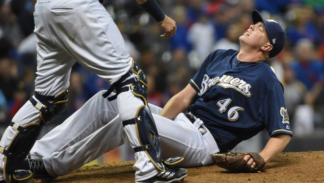 Brewers pitcher Corey Knebel clutches his leg in pain after throwing a pitch in the ninth inning against the Cubs on Thursday at Miller Park. Knebel had to leave the game.