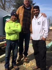 Cousins Farid Ahmad, left, and Zalmay Niazy, right, stand with friend Mike Ingebritson, center.