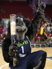 Alpha, the mascot of the Iowa Wolves, fires a T-shirt cannon into the crowd at Wells Fargo Arena during an NBA G League game.