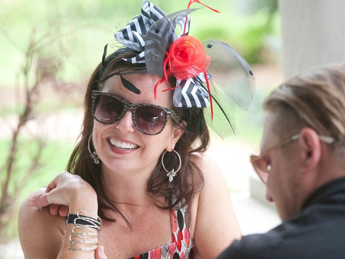 Courtney Gagel relaxes on the porch of the Peterson Dumesnil house with her friend, Matt Prybylski at the Crescent Hill Community Council's first Derby Fun and Dessert Party. Gagel was there to participate in the party's hat competition. Organizers plan to make hold the event annually. 27 April 2014