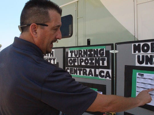 Michael Gates, the program director for one of Tulare County's mobile mental health units, checks its schedule on July 19 in Woodlake.