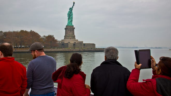FILE - In this Nov. 5, 2015, file photo, visitors view the Statue of Liberty during a ferry ride to Liberty Island in New York. The travel industry is debating whether President Donald Trump's ban on travel from seven countries will have a larger impact on tourism in the U.S. Some experts say the controversy will have no effect while others worry that it sends an unwelcoming message to travelers around the world. An op-ed piece in the Toronto Star on Jan. 30, 2017,  encouraged Canadians to boycott the U.S. for now, saying that the Statue of Liberty will still be there in a few years.