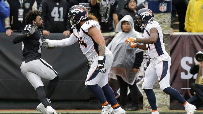 Oakland Raiders wide receiver Michael Crabtree, left, fights with Denver Broncos nose tackle Domata Peko, center, and cornerback Aqib Talib during the first half of an NFL football game in Oakland, Calif., Sunday, Nov. 26, 2017. Crabtree and Talib were ejected.