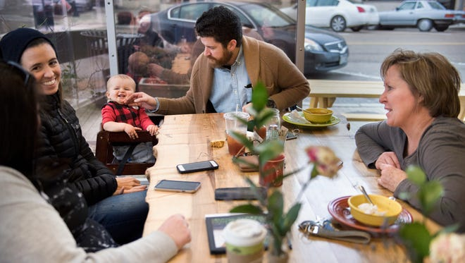 """ComeUnity CafŽe Owner Amy Crenshaw chats with customers as Lee Wilson, of Jackson, plays with his 1-year-old son, Rowan Wilson, on Tuesday, Jan. 23, 2018, at ComeUnity CafŽe in Jackson. """"We've got a great atmosphere,"""" Crenshaw said. """"We have these beautiful community tables where people can come and sit down and have a conversation with somebody they would have never crossed paths with. I've made so many friends out of customers and volunteers."""""""