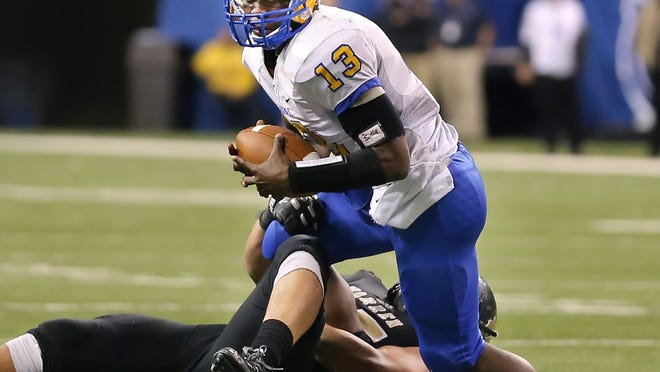 Carmel quarterback Isaac James is sacked for a loss by Warren Central defensive lineman Max Hernandez in the second half of the IHSAA Class 6A State Football Finals held at Lucas Oil Stadium on Saturday, November 30, 2013. Warren Central beat Carmel 7-6.