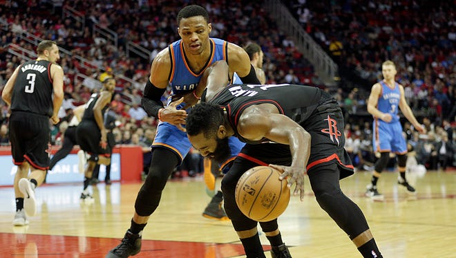 Houston Rockets guard James Harden (13) is guarded by Oklahoma City Thunder guard Russell Westbrook (0) in the third quarter at Toyota Center.