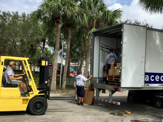 Bonita Springs firefighters help unload goods at the