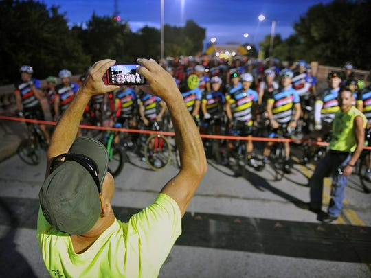 A volunteer takes a photo of a group of riders at the front of the start of the 2017 Hotter 'N Hell Hundred.