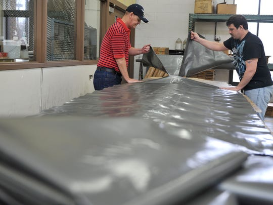 Progress Industries employees tear produce bags from a roll, one of several contracted jobs in the agency's sheltered workshop. The Mansfield agency often uses the workshop as a temporary training grounds for vocational rehabilitation clients to gain basic job skills, such as showing up on time and communicating with others, before helping them obtain a job in the community.