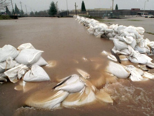 Floodwaters pour through a break in a sandbag dike