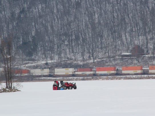 As a train passes in the background, anglers work the