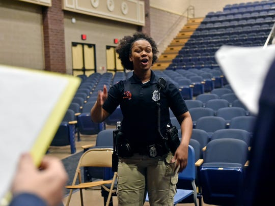 York City School police officer Britney Brooks directs students during a gospel choir rehearsal at William Penn Senior High School. The school officers are encouraged to lead activities that let students see them as more than officers.