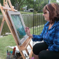Veronica Shmauz using the swimming geese and ducks as subjects as she paints the river scene on re-purposed old window sashes at the Art Guild of Menomonee Falls' Art In The Park event in Mill Pond Park on Aug. 23. Check out the calendar for  art-related events going on in the community this week.