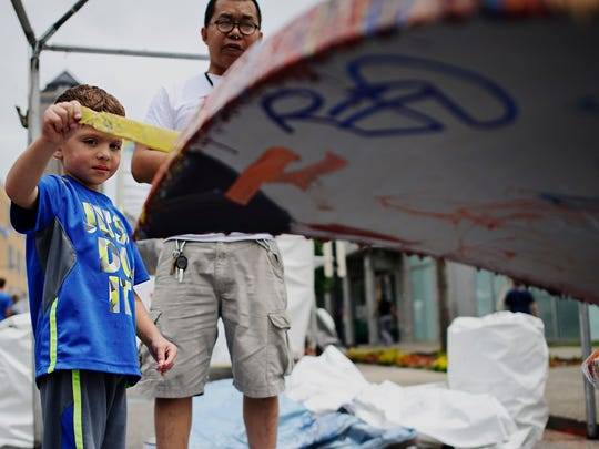 """Kadyn Denham, 5, helped artist Bounnak Thammavong paint the """"Birds of a Feather"""" sculpture at the 2015 Des Moines Arts Festival. The piece will soon be installed at the Des Moines airport."""