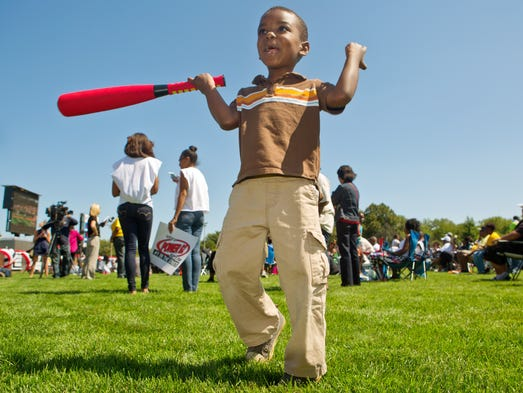 Amir Deese, 4, plays baseball with his father Aven Deese, not shown, as fans gather for a watch party for the Jackie Robinson West Little League  game in South Chicago on Thursday, August 14, 2014.