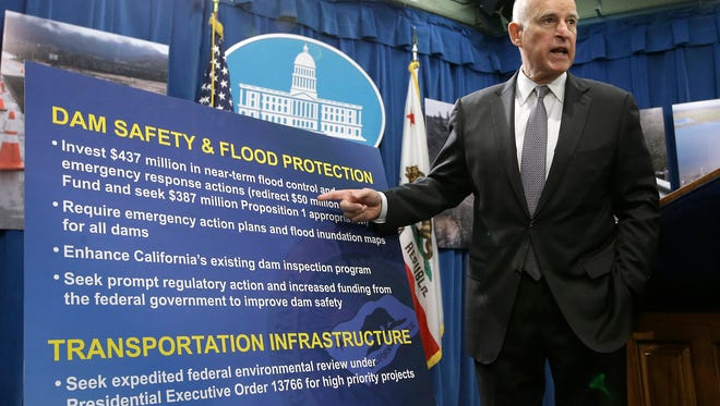 California Gov. Jerry Brown gestures Friday to a chart that show his proposal to spend $437 million on flood control and emergency response in the wake of recent storms.