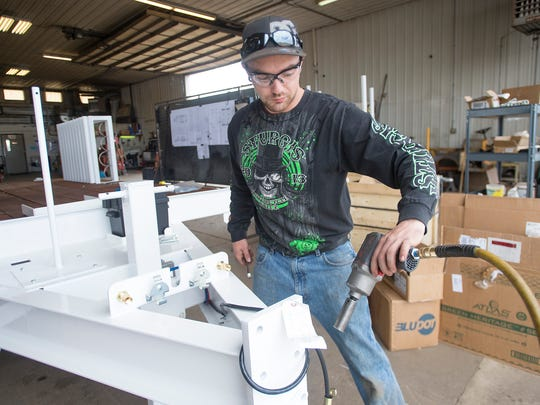 Cory Kenworthy assembles parts to a trailer in the shop at Maxey Manufacturing Co. on Lincoln Avenue on Monday, April 2, 2018.