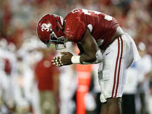 Alabama linebacker Rashaan Evans bows in celebration after he sacked Arkansas quarterback Cole Kelley during the second half an NCAA college football game, Saturday, Oct. 14, 2017, in Tuscaloosa, Ala. (AP Photo/Brynn Anderson)