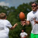 St. Clair graduate and New Orleans Saints offensive guard, Tim Lelito, catches a ball while running a drill with campers in 2014 at St. Clair High School.