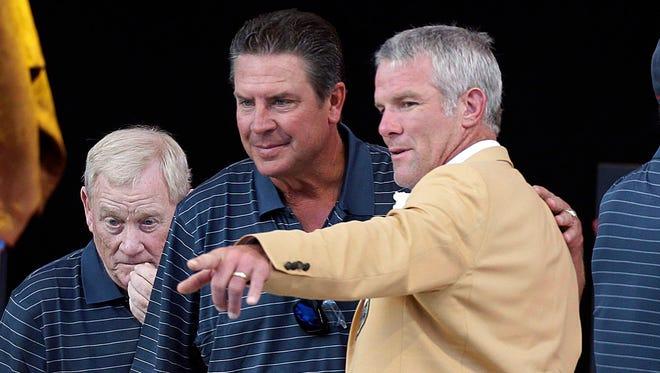 Former Green Bay Packers quarterback Brett Favre (right) chats with former quarterback Dan Marino during NFL Pro Football Hall of Fame Enshrinement Ceremony at Tom Benson Stadium.