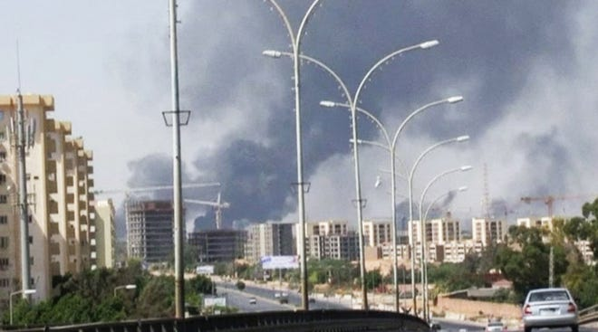 Smoke rises from the direction of the Tripoli, Libya, airport in an image captured from a video on July 13, 2014. The United States shut down its embassy in Libya on July 26, 2014.