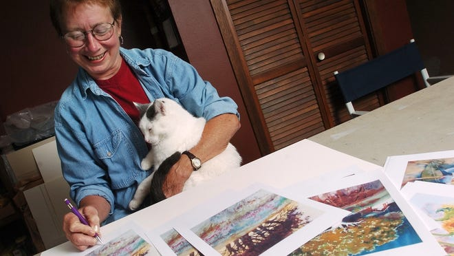 Marian Henjum's cat, Taylor, sits in her lap as she signs prints in her home studio.  (Argus Leader/Lara Neel)