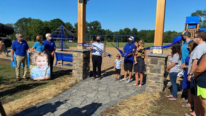 The Heiligman family and Monroe County Executive Adam Bello cut the ribbon to open Jack's Place in Webster Park.