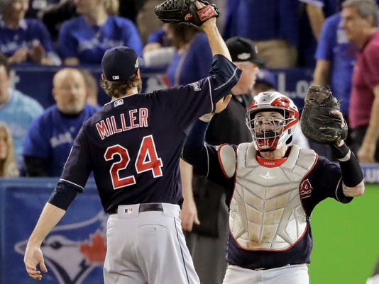Cleveland Indians relief pitcher Andrew Miller (24) and catcher Roberto Perez celebrate their 4-2 win against the Toronto Blue Jays in Game 3 of baseball's American League Championship Series in Toronto, Monday, Oct. 17, 2016. (AP Photo/Charlie Riedel)