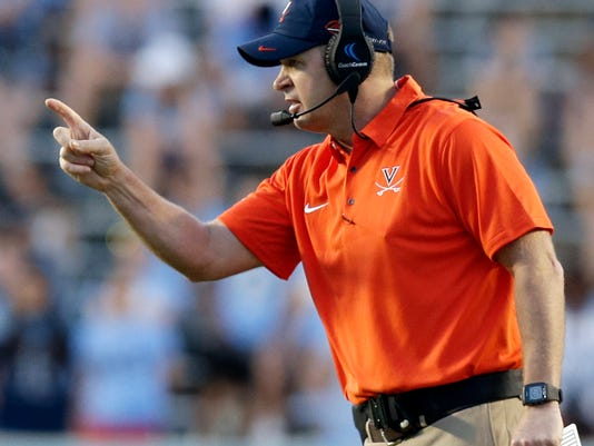 FILE - In this Oct. 14, 2017, file photo, Virginia head coach Bronco Mendenhall directs his team during the second half an NCAA college football game against North Carolina in Chapel Hill, N.C. Miami's Mark Richt isn't the only Atlantic Coast Conference coach who is having success in his second season. Virginia have qualified for a bowl game for the first time since 2011.  (AP Photo/Gerry Broome, File)