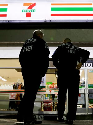 U.S. Immigration and Customs Enforcement agents serve an employment audit notice at a 7-Eleven convenience store on Jan. 10, 2018, in Los Angeles.