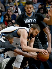 Memphis Grizzlies Marc Gasol, center, battles for the ball with Minnesota Timberwolves Kris Dunn, left, and Karl-Anthony Towns.