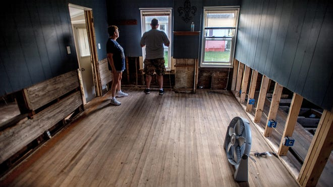 Amy Hutchens, left, and her boyfriend Randy Westlake look over Hutchens' property at 111 N. Church St. in Roanoke. Hutchens had recently bought the house only to see it completely flooded and largely destroyed in a heavy rainstorm in July.