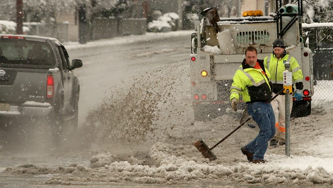 Bremerton city worker McKee Mosher jumps out of the way of flying slush as he helps clean the drainage area Monday at 11th Street and Warren Avenue.